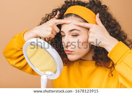Young girl squeezes pimple on the fer face in front of a bathroom mirror. Beauty skincare and wellness morning concept isolated over beige background. #1678123915