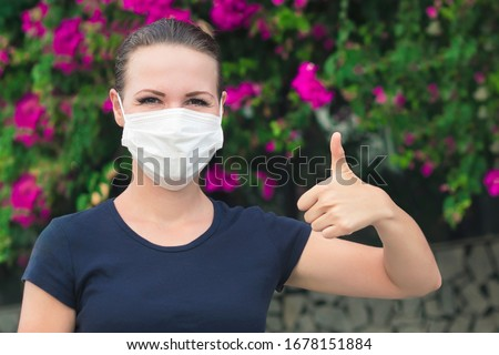 Happy positive girl, young cheerful beautiful woman in protective sterile medical mask on her face looking at camera outdoors, smiling, show thumb up, like gesture. Happy end. Pollen allergy #1678151884