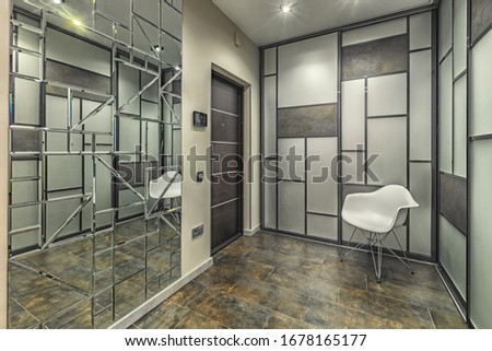 Empty residential house entrance with closed doors build in closets with mirrors #1678165177