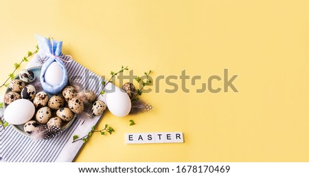 Overquail eggs with young sprigs of green plants on a light background. Holiday content, a place for text #1678170469
