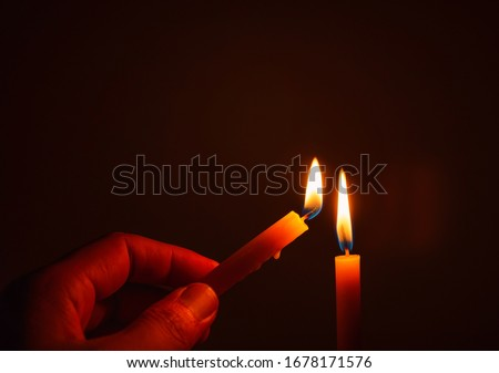 The hand that is lighting candles in the dark With burning candles shining the light at night  Design for the background, Burning candles on black background, Candle in hand, Candles in the dark. #1678171576