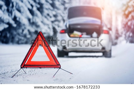 Winter and vehicle broken concept - detail of red warning triangle with a broken car on snowy road.