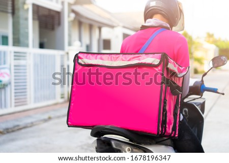 Motorbike delivery man wearing pink uniform and ready to send food.Delivering Food In City.Delivery man of takeaway with isothermal food pink case box driving find home.Express food delivery service. #1678196347