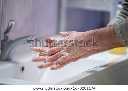 man washes his hands with soap at home . The concept of virus protection. hand hygiene. Fight against microbes, viruses, bacteria, covid-19. Stay home. Quarantine. World pandemic. #1678201174