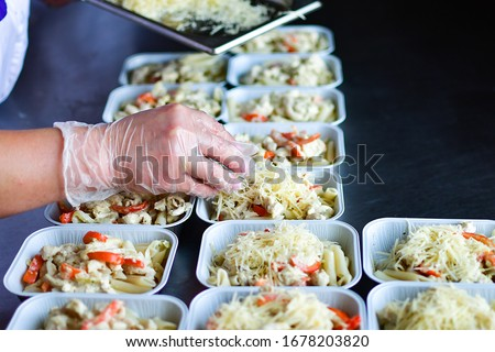 takeaway chicken salad with vegetables and cheese food delivery. preparing portions in containers. service food order online delivery in quarantine covid-19. airline food. airline meals and snacks #1678203820