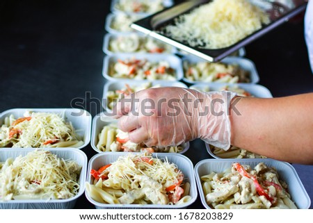 takeaway chicken salad with vegetables and cheese food delivery. preparing portions in containers. service food order online delivery in quarantine covid-19. airline food. airline meals and snacks #1678203829