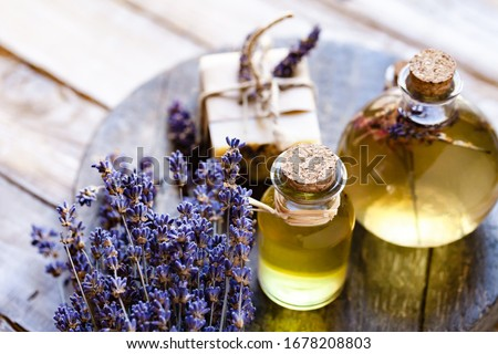Concept of natural organic oil in cosmetology. Moisturizing skin care and aromatherapy. Gentle body treatment. Handmade soap. Atmosphere of harmony relax. Wooden background, lavender flower copy space Royalty-Free Stock Photo #1678208803