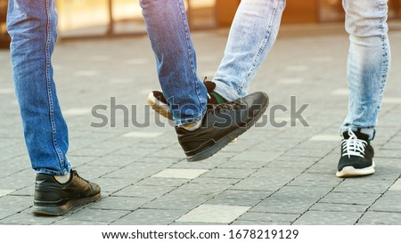 Foot shake style of greetings. Prevention of fight against pandemic. Quarantine methods to control spread of coronavirus. New greeting style during coronavirus outbreak. People bump feet outdoors. Royalty-Free Stock Photo #1678219129