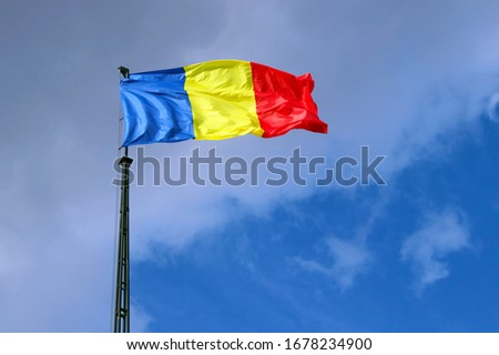 Flag of Romania on mast, in front of the blue sky. Blue background with clouds #1678234900