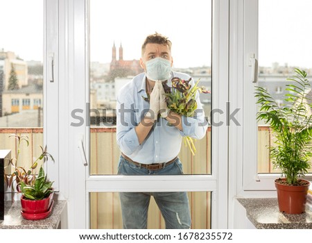a man in a medical mask and medical gloves with a bouquet of wilted tulips stands on the balcony of a city apartment. Quarantine. Coronavirus pandemic. The concept of a date in an epidemic. #1678235572