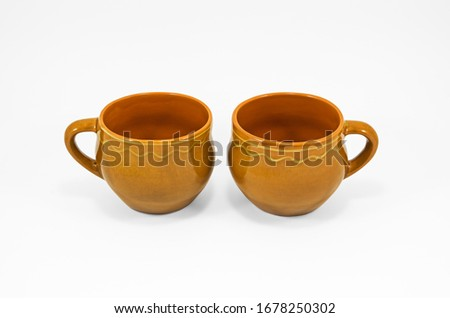 Two empty homemade clay cups of orange color isolated on white background #1678250302