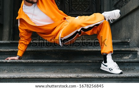 Closeup photo of a young man in bright streetwear dancing hip hop on the stairs in a row building. Professional street dancer dancing break dance on the street. Cropped photo. Background.