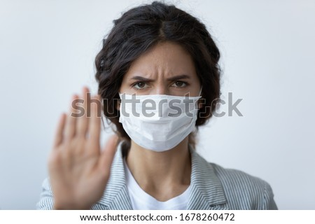 Head shot angry woman in mask stretched arm as sign of stop COVID-19 follow quarantine rules, stay at home, avoid physical contact, wash hands keep distance, prevent spread of epidemic disease concept #1678260472