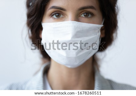 Close up portrait of beautiful 30s young millennial woman cover her face wearing facial medical blue mask, anti-coronavirus COVID-19 pandemic infectious disease outbreak protection, healthcare concept #1678260511