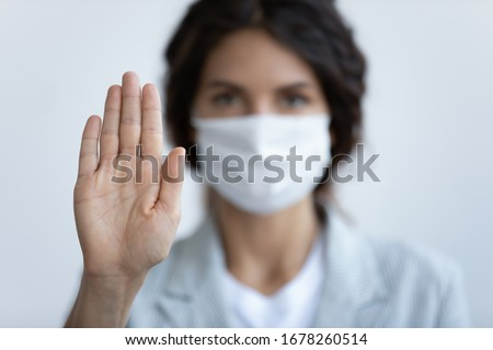 Help stop spreading globally corona virus pandemic infectious disease outbreak. On background woman in mask focus on stretched hand as symbol of keep distance avoid communication, healthcare concept Royalty-Free Stock Photo #1678260514