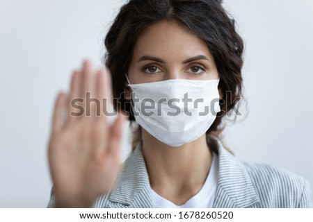 On blue background close up focus on female face in mask looking at camera, out of focus stretched hand. Help slow outbreak of corona virus, stay at home, keep distance and hygiene conceptual poster #1678260520