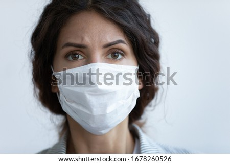 Close up front view concerned woman face portrait wear facial mask pose on blue studio background look at camera feels afraid. COVID-19 sars-cov-2 epidemic pandemic virus outbreak protection concept #1678260526