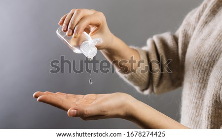 Hand sanitizer alcohol gel rub clean hands hygiene prevention of coronavirus virus outbreak. Woman using bottle of antibacterial sanitiser soap gel. #1678274425
