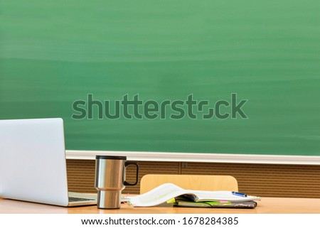 Photo of laptop on professor desk with tumbler and book against black board in classroom there are no classes taking place due to the corona covid-19 infection #1678284385