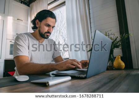 Workplace at home. A man works at a laptop at home, sits at a table in the living room during the day. Work from home. #1678288711