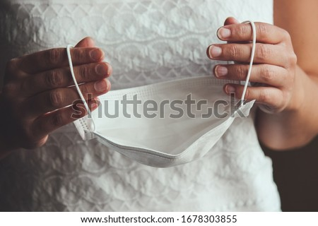 Bride hands holding white medical face mask. Woman in wedding dress during the Coronavirus epidemic. Cancelled or postponed weddings caused by COVID-19 outbreak. Coronavirus concept, conceptual photo. #1678303855