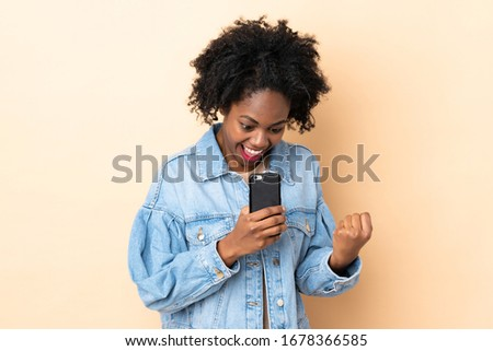 Young African American woman isolated on beige background surprised and sending a message #1678366585