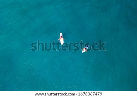 Two surfers in the ocean waiting a wave. shot from above
