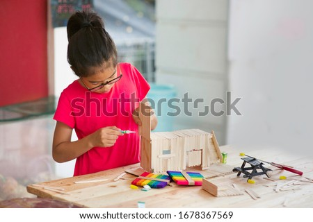 Asian girl using glue to fix popsicle sticks project. Child crafting using sticks.Young female homeschooler making craft using wooden stick on table in outdoor.Mini picnic bench.Homeschooling. Royalty-Free Stock Photo #1678367569