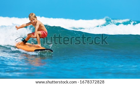 Happy baby boy - young surfer learn to ride on surfboard with fun on sea waves. Active family lifestyle, kids outdoor water sport lessons, swimming activity in surf camp. Summer vacation with child. Royalty-Free Stock Photo #1678372828