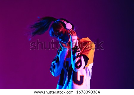 Stylish fashion teenager model wearing hoodie and headphones listening dj music dancing in purple neon lights. Young teen girl enjoy cool music 90s party mix in violet studio background. Copy space. #1678390384