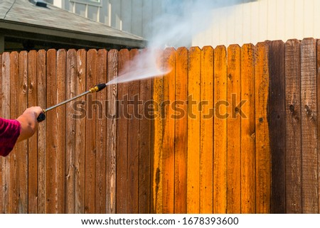 high Pressure Washing the Wooden Fence , Old into New , Cleaning my fence with a Pressure Washer Royalty-Free Stock Photo #1678393600