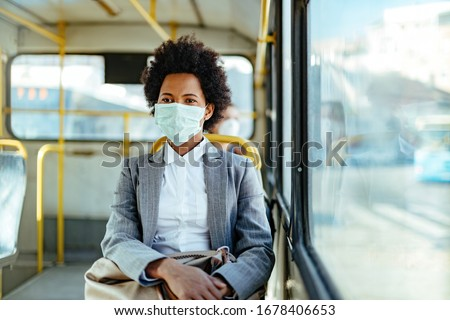 African American businesswoman wearing protective mask while traveling by public transportation.  #1678406653