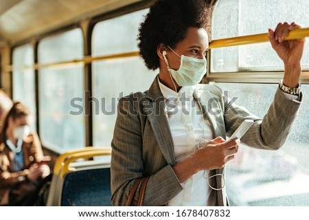Black businesswoman with protective face mask using smart phone and looking through the window while commuting by bus.   #1678407832