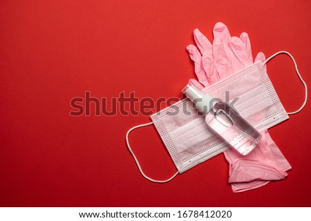Medical background red. Medical surgical mask, sanitizer gel and lab gloves on Virus protection equipment. Dangerous illness corona virus. Novel Coronavirus 2019-nCoV Royalty-Free Stock Photo #1678412020