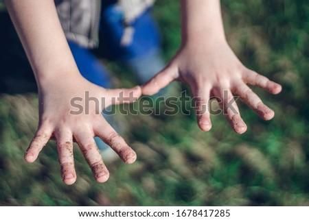 Small child's outstretched dirty hands on the green grass background in the park. Hygiene concept, close up. #1678417285