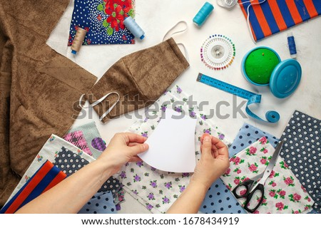 Painting, fabrics and sewing accessories for sewing an anti-virus mask. Zero waste and quarantine concept. Homemade facemask against virus infection in detail. Top view Royalty-Free Stock Photo #1678434919