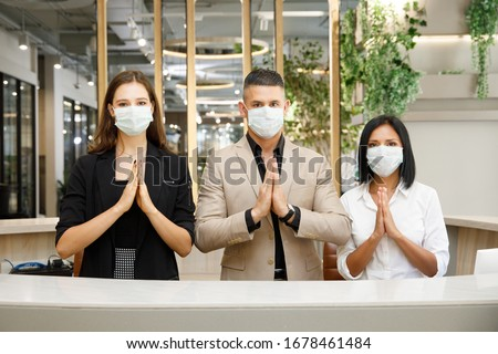 hotel receptionist wearing mask to protect from conronavirus covid 19 having new practice of greeting with thai wai, new greeting practice in coronavirus covid 19 pandemic  #1678461484