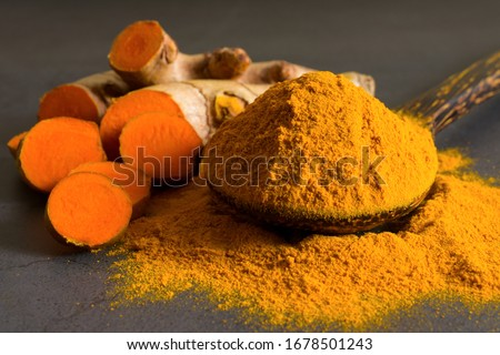 Turmeric (curcumin) powder in a wooden ladle and fresh rhizome on a black background,For spices and medicine. #1678501243