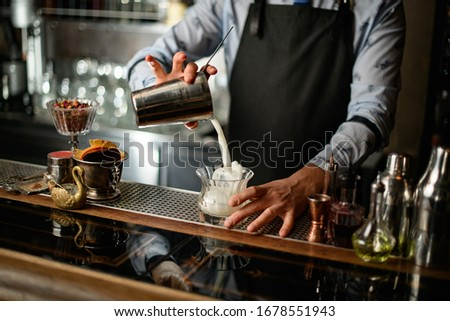 Bartender gently pours cocktail from shaker into glass with ice. Different glasses, bottles and shakers stand on bar counter. #1678551943