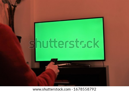 A white male hand using remote controller over a green screen television late in the night.green screen on smart tv.Place for your advertisment.modern television set-Athens Greece March 23 2020 #1678558792
