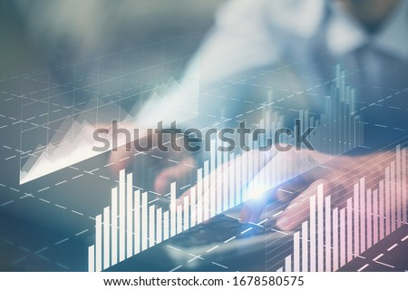 Forex graph with businessman working on computer in office on background. Concept of hardworking. Multi exposure. #1678580575