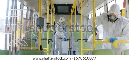 HazMat team in protective suits decontaminating public transport, bus interior during virus outbreak #1678610077