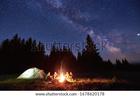 Night camping near bright fire in spruce forest under starry magical sky with milky way. Group of four friends sitting together around campfire, enjoying fresh air near tent. Tourism, camping concept. #1678620178