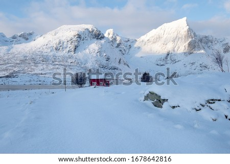 Lonely cabin surrounded by mountains and ocean.  Built in typical norwegian architectural style.  Architecture connected with nature.  Located in Lofoten islands, northern Norway. Picture taken