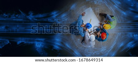 Top view of architectural engineer working on his blueprints with documents on construction site. meeting, discussing,designing, planing. Road traffic an important infrastructure Royalty-Free Stock Photo #1678649314