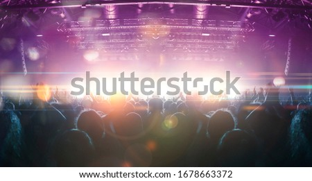 Concert crowd point of view inside a large concert hall during a music festival, the lit stage is visible. Royalty-Free Stock Photo #1678663372