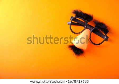 Overhead glasses, nose and mustache for April 1, April Fool's Day, on orange background Royalty-Free Stock Photo #1678719685