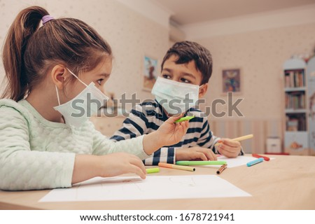 Cute children boy and girl in medical mask is sitting at home in quarantine. Entertainment for the children during quarantine - drawing. Self isolation.