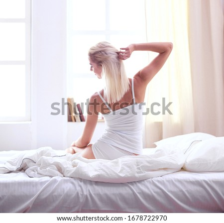 Woman stretching in bed after wake up, back view #1678722970