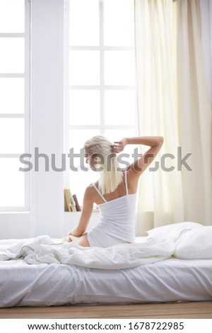 Woman stretching in bed after wake up, back view #1678722985